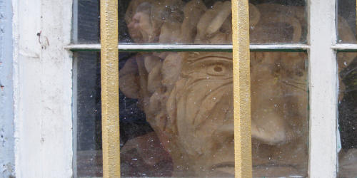 carved wooden face behind bars