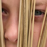 boy looking through reeds