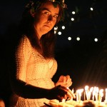 woman against the dark with birthday candles