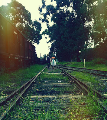 bride and groom walking train tracks